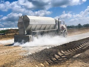 A spreader truck spreads product over the problematic soil